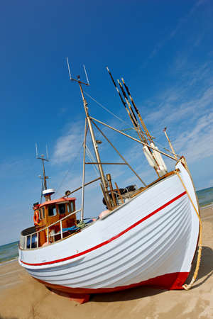 meer: A photo of a Danish fishing boat at the beach Editorial