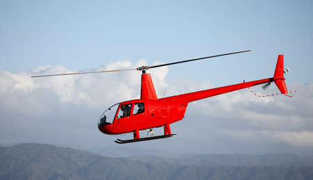 A telephoto of a red helicopter and blue sky