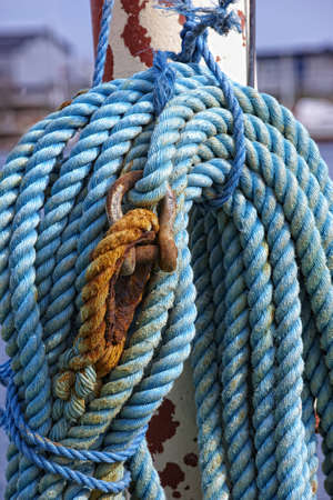 belaying: blue boaters rope on belaying cleat, yacht equipment