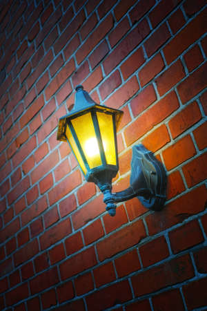 aglow: a photo of an outdoor lamp on a brick wall