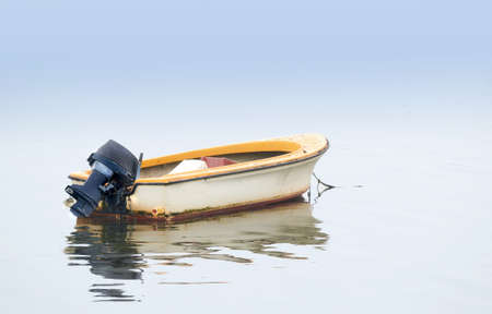 rowing boat: A photo of Small boat an early foggy morning