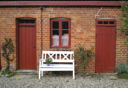door leaf: A photo of a bench in front of an very old farmhouse