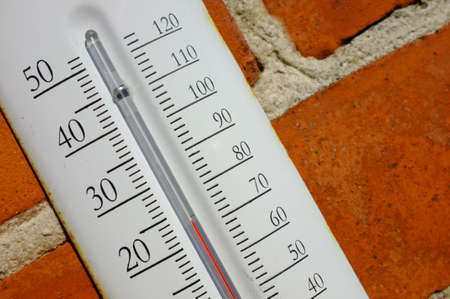 coldly: A photo an outdoor thermometer on brick wall
