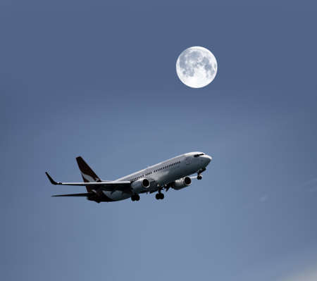 Airplane in the night sky and moon Stock Photo - 17355666