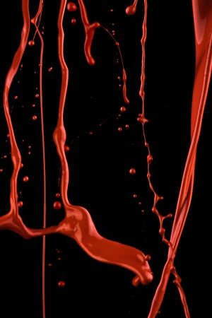Splashes of red paint. Isolated paint on black in a movement. Standard-Bild