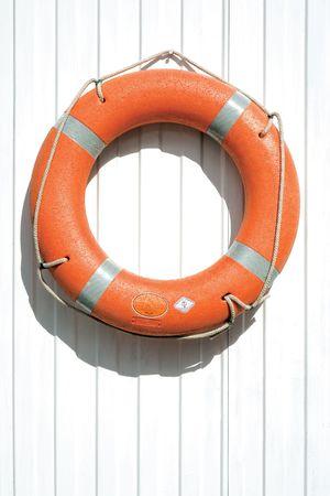 salvavidas: Naranja lifebuoy en el cerco. Una vista de una naranja lifebuoy o dispositivo de salvamento en una cerca blanca. Foto de archivo