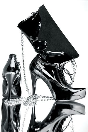 Fancy shoe and silver bag. Fancy black and silver shoe with a silver bag on a reflective mirror surface in high contrast. photo