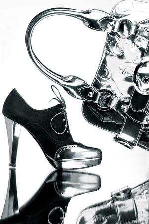 Fancy shoe and silver bag. Fancy black and silver shoe with a silver bag on a reflective mirror surface in high contrast. Stock Photo - 4081369