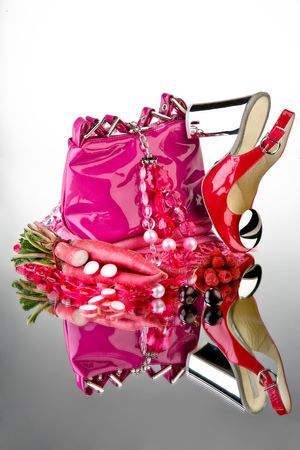 metaphorical: Pink shoes and purse. Pink shoes and purse with accessories and vegetable on a reflective mirror table.
