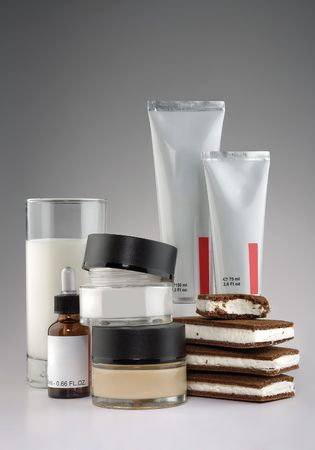 Cosmetics, milk and ice cream. A glass of milk, ice cream sandwiches, tubes, bottle and jars of medical cosmetics.
