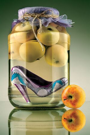 entice: Shoe in a jar of apples. A shoe at the bottom of a jar of apples.