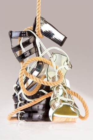bagged: Glamorous Footwear. An view of glamorous female footwear in an abstract arrangement tied with a rope. Stock Photo