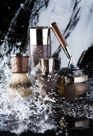 Shaving accessories and water.  Close up of male shaving accessories with water background and splashes. photo
