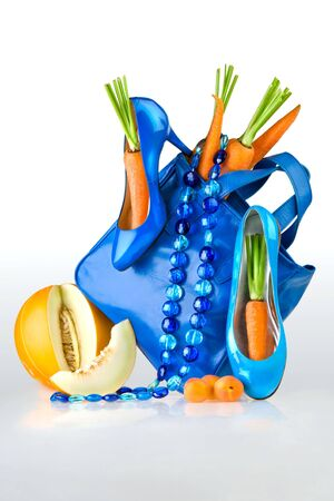 Blue purse, shoes and jewelry.  A still life of blue accessories, shoes, purse and necklace with carrots and melon. photo