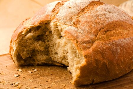 mouth watering: Fresh bread with ear of wheat. Still life view of freshly baked bread with part broken off, and ear of wheat.