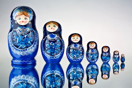 Babushka Nesting Dolls.  A view of blue colored Russian babushka nesting dolls on a glass surface. Stock Photo