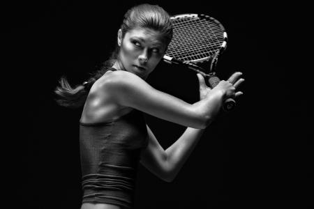 tennis: Joueur de tennis f�minin. Femme joueuse de tennis la tenue de raquette derri�re la t�te, isol� sur un fond noir.