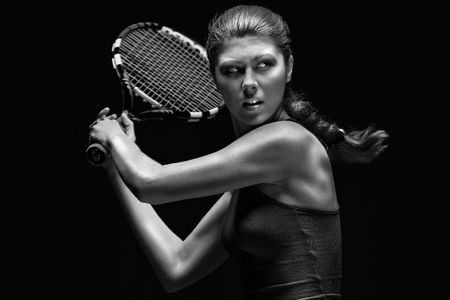 Female tennis player.  Female tennis player holding racket behind head, isolated on black background. photo
