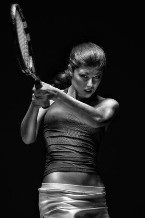 Female tennis player.  Female tennis player holding racket behind head, isolated on black background. Stock Photo
