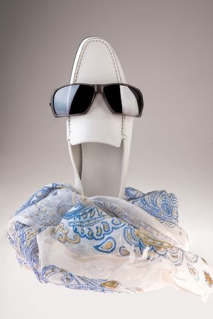 lighthearted: Humorous smiling shoe. A whimsical, lighthearted view of a smiling white shoe wearing sunglasses with a light print scarf in the foreground Stock Photo