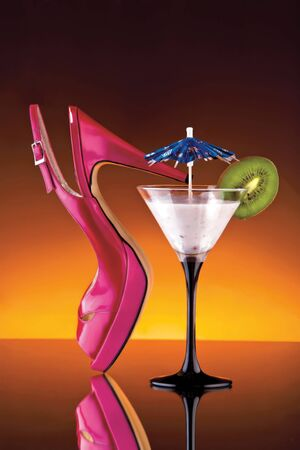 garnishing: Womans shoe and cocktail. A colorful view of a womans pink high heel shoe and a cocktail glass garnished with a paper umbrella and a slice of kiwi.