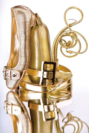 haversack: Glamorous gold accessories. Glamorous gold shoes and accessories on a reflective surface.
