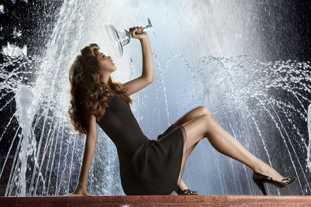 waterspout: Woman posing by fountain. Fashionable woman holding vase posing in front of water fountain. Stock Photo