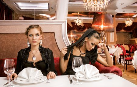Dining Beauties. A portrait of two beautiful women on a table of a luxurious restaurant, for dinner. photo