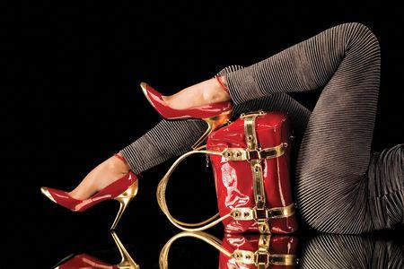 Bijpassende rode schoenen en tas. Een studio-weergave van de sexy benen van een vrouw die stijlvolle rode schoenen met hoge hakken draagt die passen bij haar mooie rode tas. Zwarte achtergrond. Stockfoto