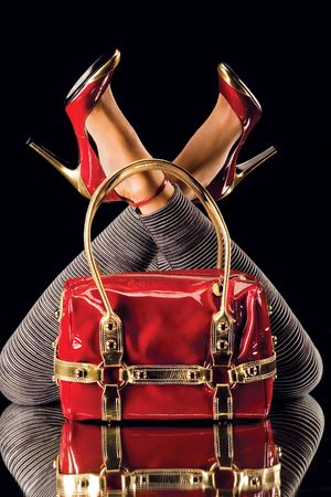 designer bag: Red shoes and bag. Woman wearing red shoes with legs crossed and red and gold purse on reflective mirror.