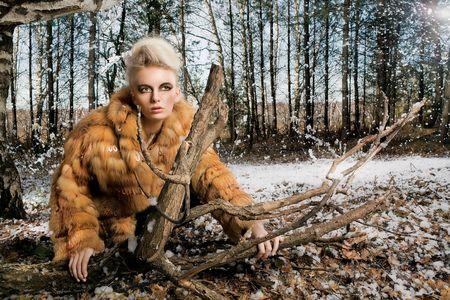 bontjas: Vrouw Slijtonderdelen bontjas. Vrouw draagt een bontjas in het bos. Stockfoto