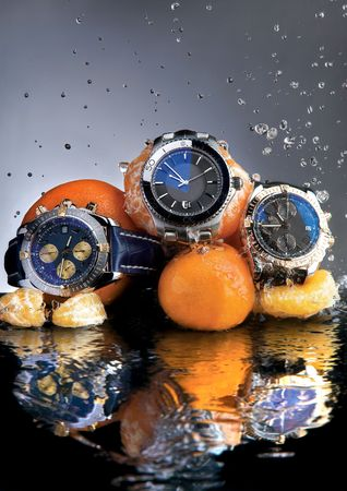 wrist: Orange Watches.  An abstract picture of designer watches and oranges submerged in water. Stock Photo