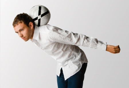 Man balancing football. A man dressed in a white shirt and blue jeans balances a white football on the back of his neck as he leans forward
