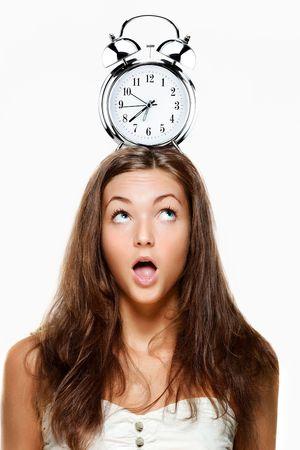 puntualidad: Retrato de una mujer joven con un reloj de alarma sobre su cabeza.  Fondo blanco