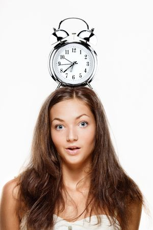 Woman with an alarm clock on her head, showing morning time. photo