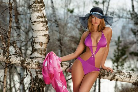 seduction: Sexy young woman in purple bikini and fashionable hat outdoors with snowy forest background.