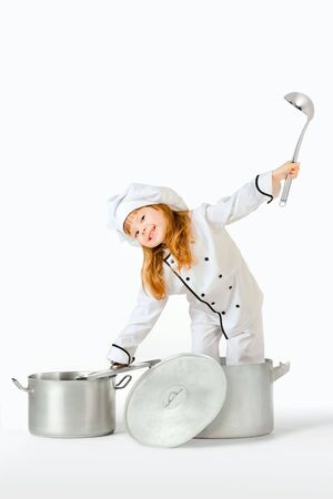 cooking chef: A girl dressed as a cooking chef, playing with large pots and pans.