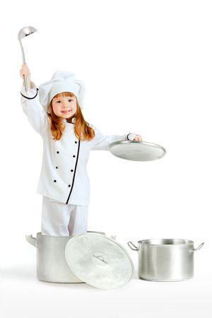 Een meisje gekleed als koken chef, spelen met grote potten en pannen.