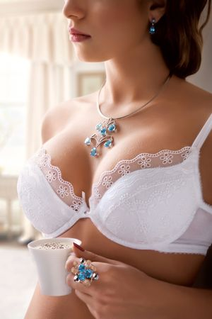 caffe: Ultra sexy woman wearing bra and jewelery holding a cup of cappuccino Stock Photo