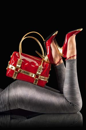 Red handbag and high heel shoes on a womans legs against a black background.