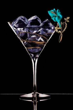 jeweller: A jeweller flower is twisted around martiny glass with dropped in ice cubes