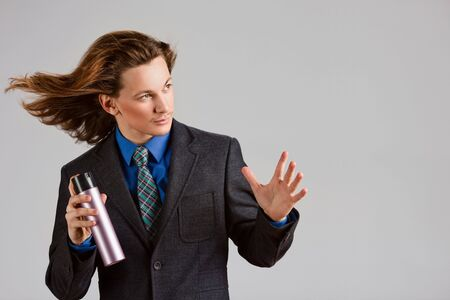 styler: Male stylist with spray can and wind blowing through hair.