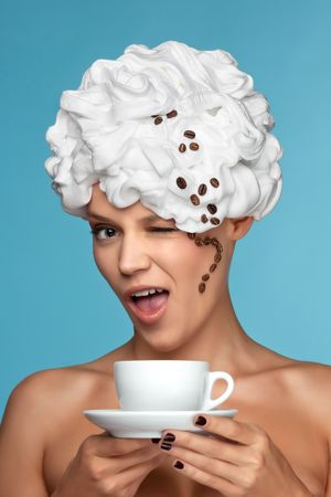 Portrait of a woman holding a coffee cup with hair covered in white foam and coffee beans down the side of her face, representing cup of cappuccino. Stock Photo - 7488430