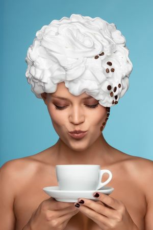 Portrait of a woman holding a coffee cup with hair covered in white foam and coffee beans down the side of her face, representing cup of cappuccino. photo