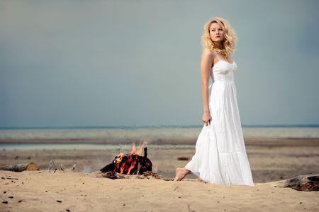 A woman wearing a white dress on the beach near a campfire. photo