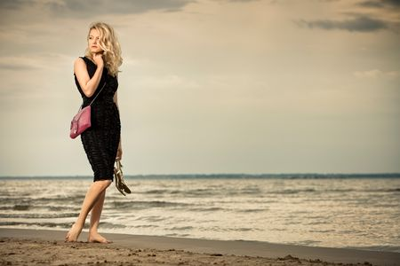 handbags: Fashionable young woman in dress with handbag paddling on sandy beach.