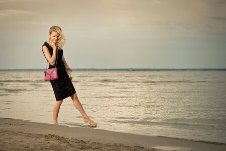 Fashionable young woman in dress with handbag paddling on sandy beach. photo
