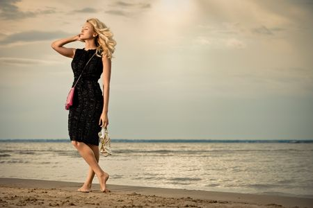 Fashionable young woman in dress with handbag paddling on sandy beach.