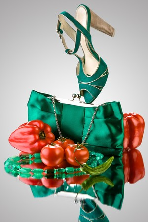 dolly bag: Veg fashion. A close-up of a blue purse, high-heeled shoe, beads and vegetables.