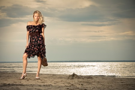 On the beach. A young pretty lady standing against the background of a seashore. photo